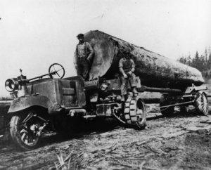 3 wheel tractor hauling a big log