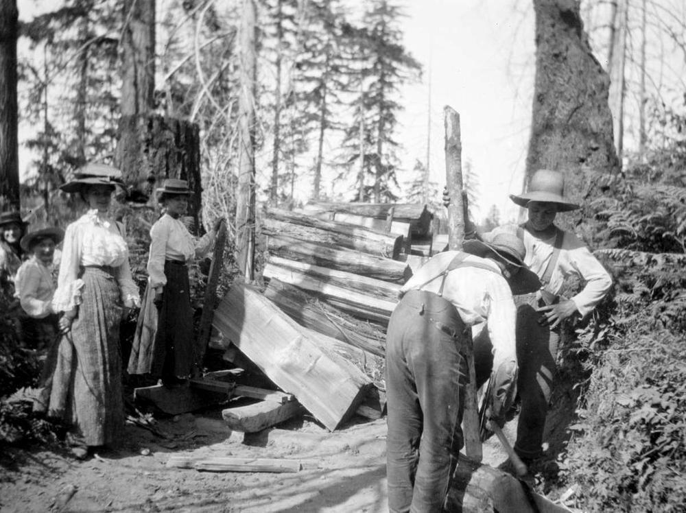 1904 Jul 11 A group of women watch as two men prepare cedar bolts.