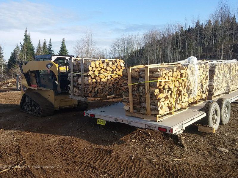 Loading an aluminium flat deck trailer with palletized firewood.
