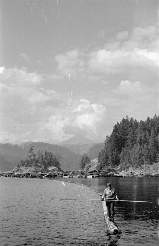 1938 Man walking on a log boom.