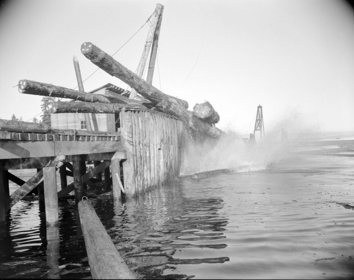 1940s Logs falling off a wharf into the water at H.R. MacMillan Co.