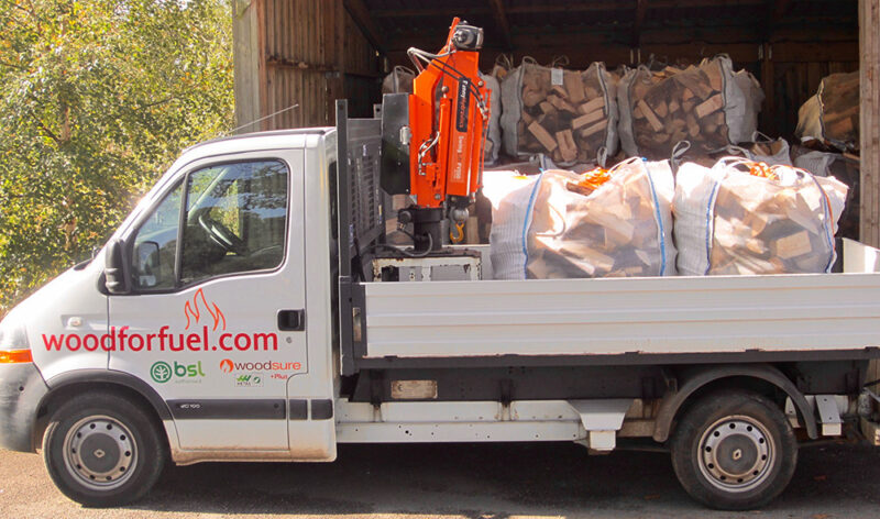 Firewood delivery truck with boom for off loading bagged firewood.