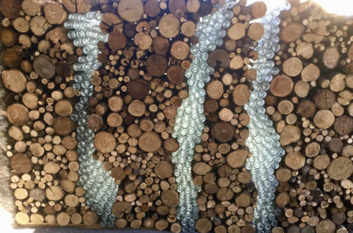 Bottles intergrated with firewood pile.