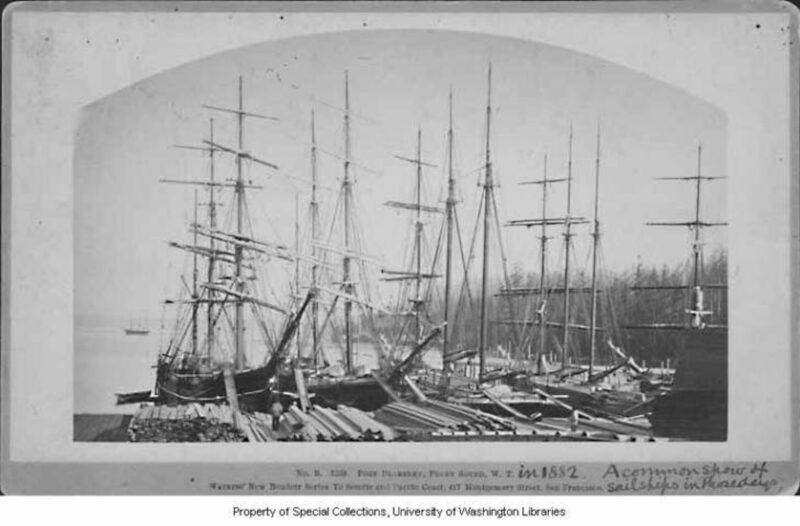 Sailing ships loading lumber.