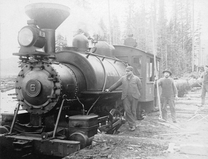 1900 Men standing beside railway engine pulling logs.