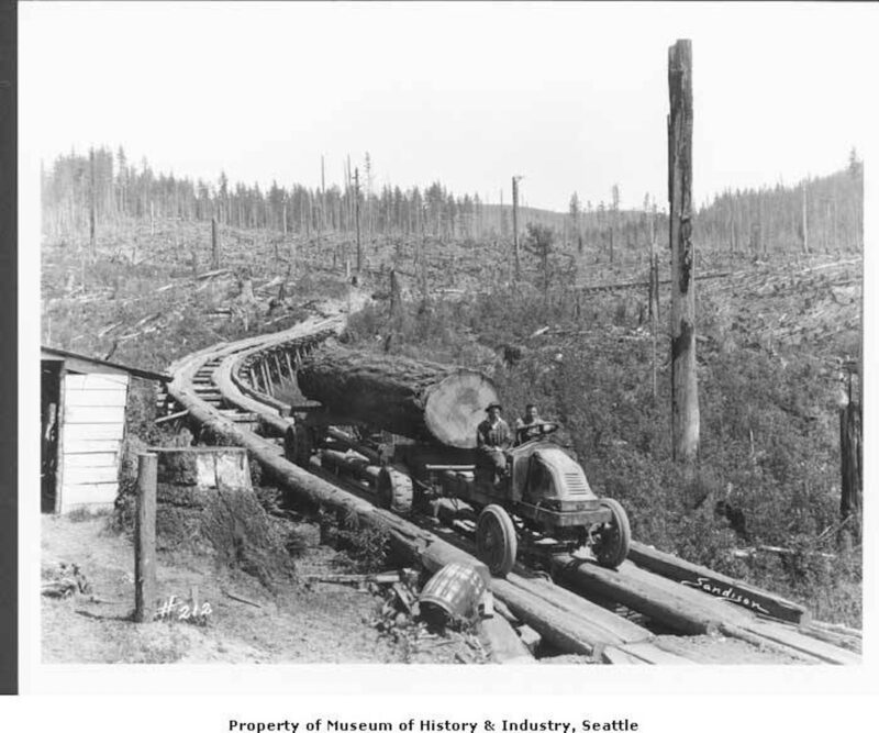 1925 Kelly-Springfield truck hauling logs on fore-and-aft plank road.
