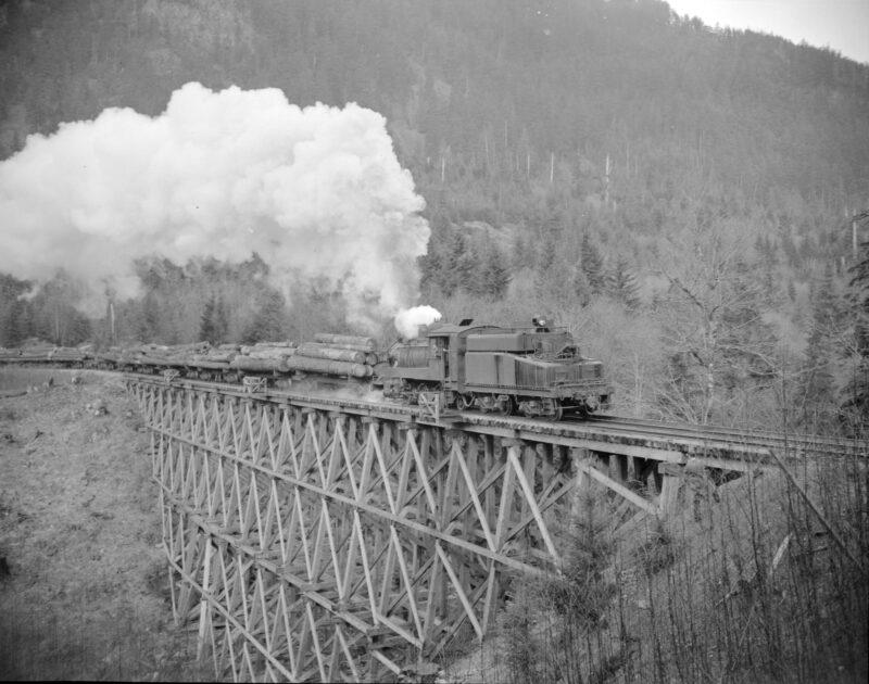 1940-1948 Train pulling a load of logs over a trestle bridge.