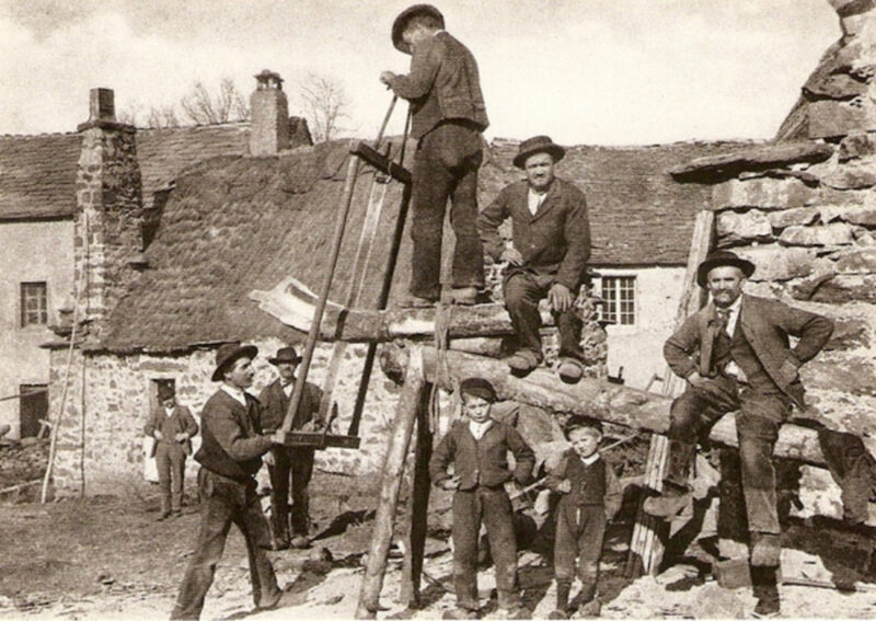 Carpenters making lumber from a curved piece of timber.