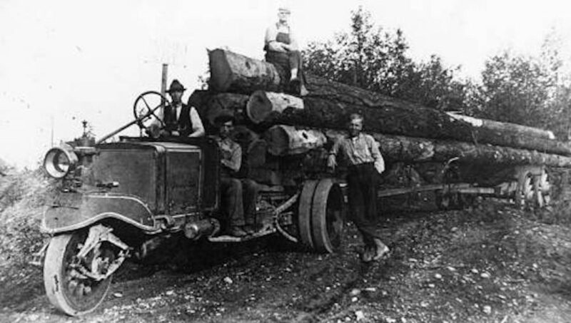 Men trucking logs out of the woods with a 3 wheeled truck.