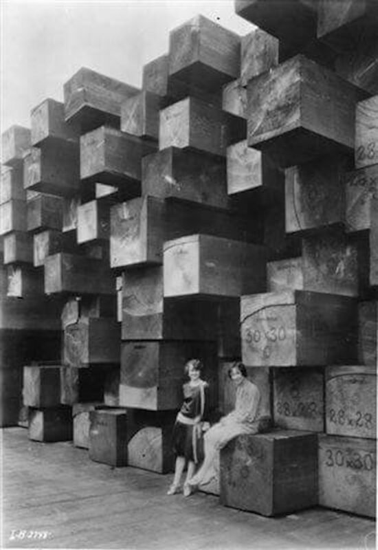 1930s Two women pose near stacks of large cants.