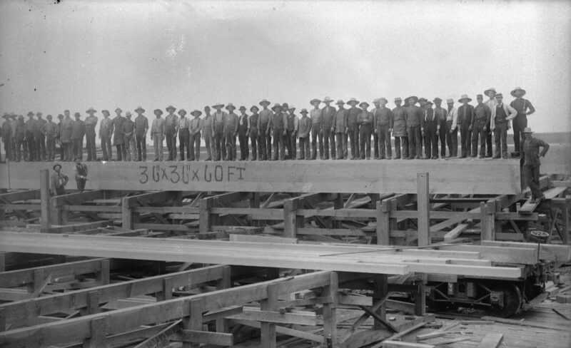 1900s Row of workers standing on a BC toothpick, 36x36 inches x 60 ft long at Hastings Sawmill.