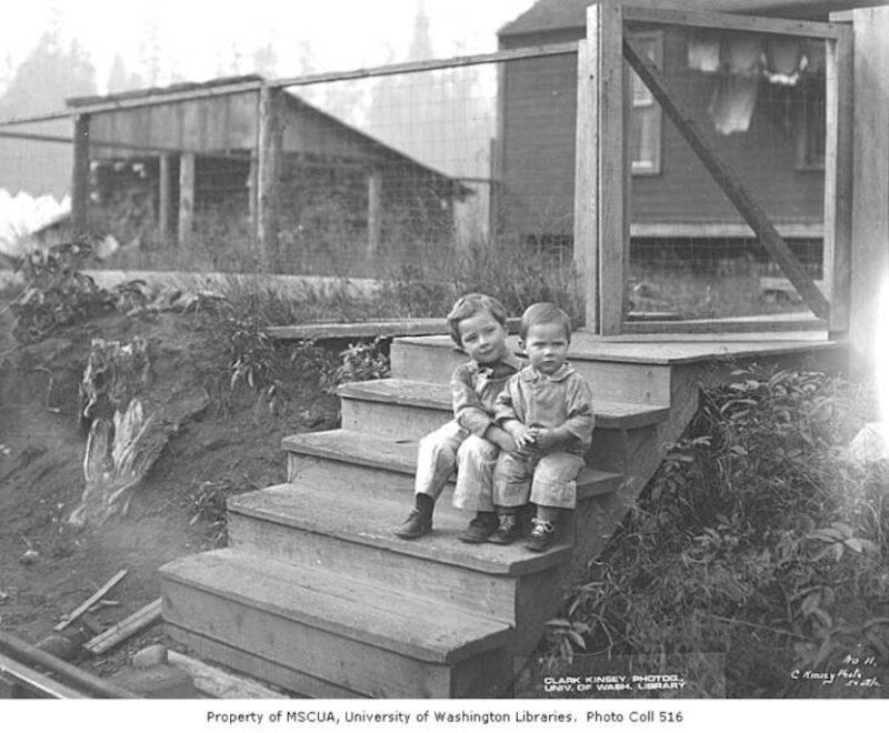 1928 Boys sitting on steps at railroad logging camp.