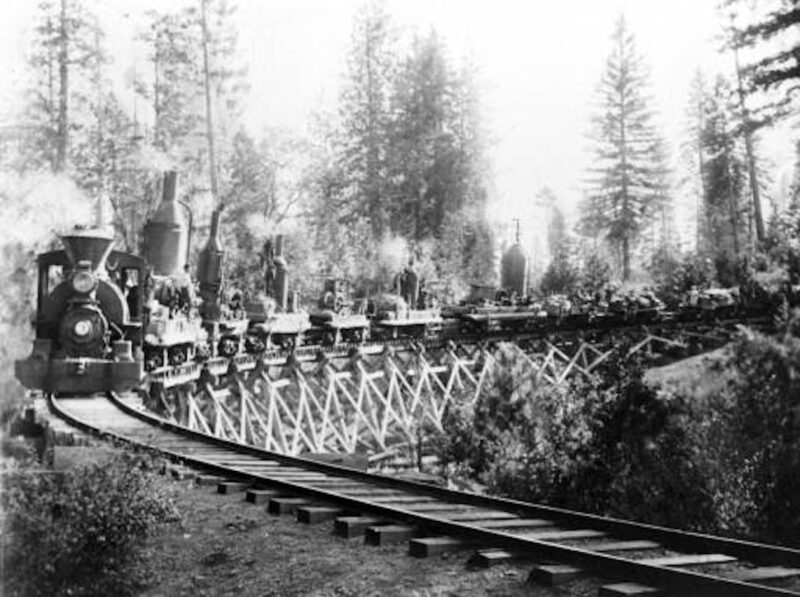 1908 Oct 7: View of a logging train hauling logs and equipment through Tehama County, CA.