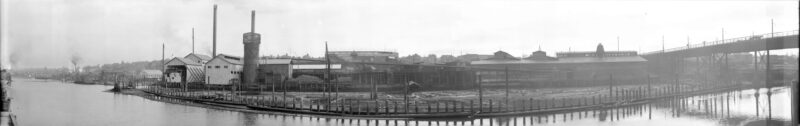1924 A panoramic waterfront view of J. Hanbury and Co. Mill, False Creek. Advertsiing includes 'John W. Boyd Insurance, Standard Bank Bldg', 'Spalding's Athletic Goods 424 Hastings St. W.', 'Pacific Milk'.