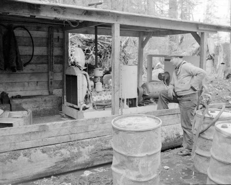 1945 Man looking at an electric tree faller in the Queen Charlotte Islands