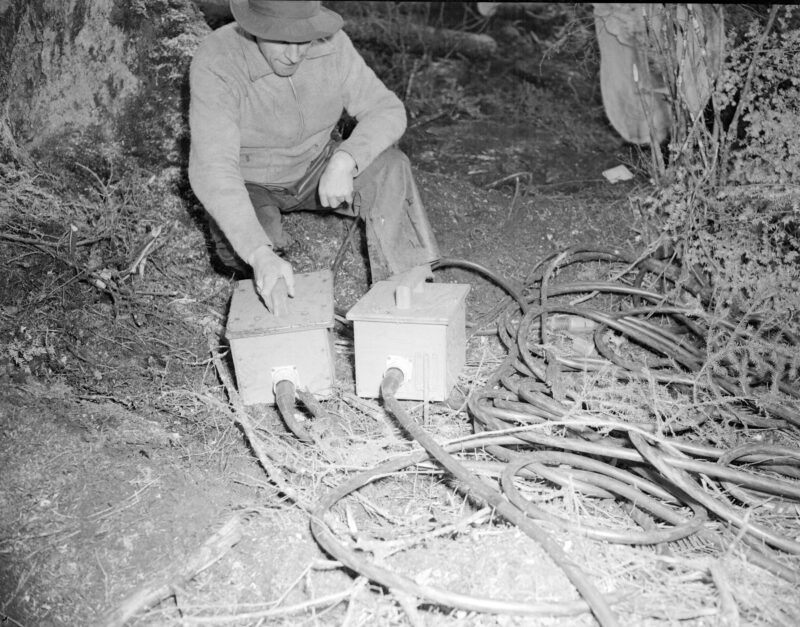 1945 Man looking at power saw connections in the Queen Charlotte Islands.
