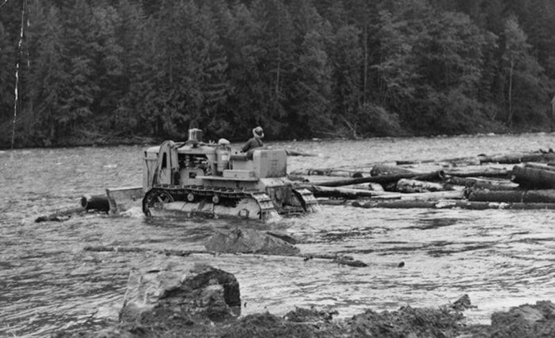Tractor crawler pushing logs out to make a river raft.